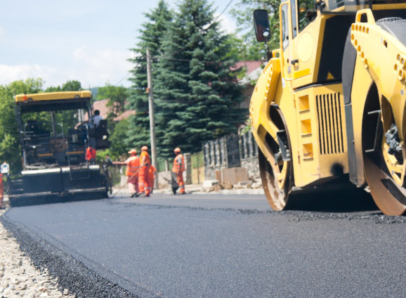 Construction workers paving a road
